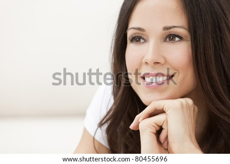 Portrait of a beautiful brunette young woman with perfect teeth smiling and resting on her hands - stock photo