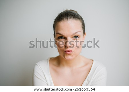 Portrait of a beautiful brunette young woman with pouching lips, white background - stock photo