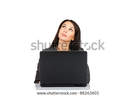 Portrait of a beautiful business woman sitting at the desk with laptop think looking up to empty copy space, isolated over white background