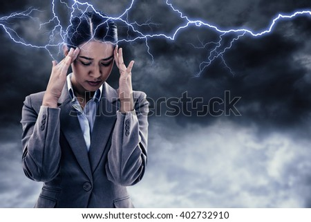 Portrait of a beautiful businesswoman having a headache against blue sky with white clouds - stock photo