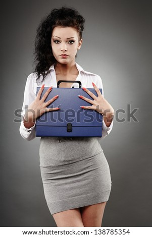 Portrait of a beautiful businesswoman posing on gray background - stock photo