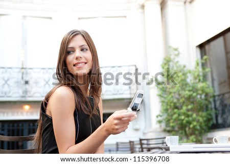 Portrait of a beautiful businesswoman using a cell phone while sitting in a classic coffee shop, smiling outdoors. - stock photo