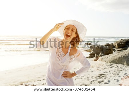 Portrait of a beautiful carefree woman walking on beach with sun dress and hat - stock photo