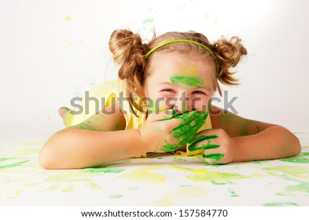 Portrait of a beautiful child enjoying his painting - stock photo