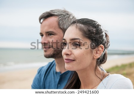Portrait of a beautiful couple at the beach wearing casual clothes  - stock photo