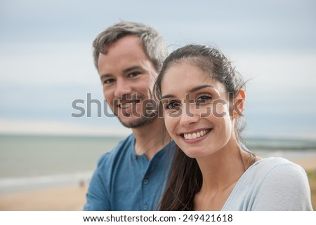 Portrait of a beautiful couple at the beach wearing casual clothes and looking at the camera - stock photo