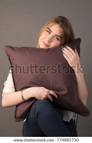 Portrait of a beautiful cute girl sitting with a pillow