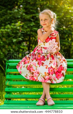 portrait of a beautiful cute young girl in a smart dress with a bouquet of flowers on a summer evening - stock photo