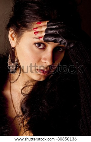 portrait of a beautiful dark-haired tanned girl on a black background
