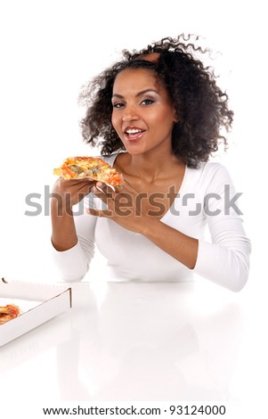 portrait of a beautiful dark-skinned woman with a piece of pizza in her hands in a white dress in the studio - stock photo