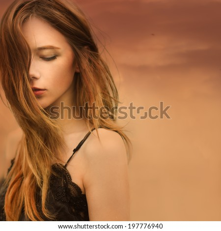 portrait of a beautiful dreamy girl on a background of red sky