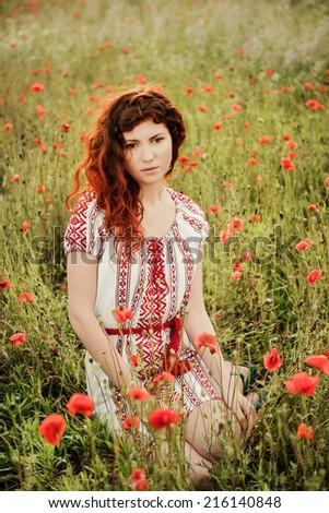 Portrait of a beautiful dreamy girl sitting in the poppies field  in Ukrainian national dress - stock photo