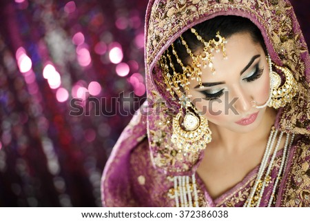 Portrait of a Beautiful Elegant Female Model in Traditional Ethnic Indian Asian Bridal  Costume with Makeup and Heavy Jewellery - stock photo