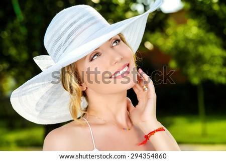 Portrait of a beautiful elegant woman in light white dress and hat standing in the summer park. Beauty, fashion. - stock photo