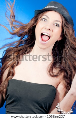 Portrait of a Beautiful elegant woman with hat excited and happy smiling presenting or showing with eyes and mouth wide open  in studio on the blue background