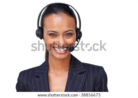 Portrait of a beautiful ethnic businesswoman with a headset on smiling at the camera - stock photo