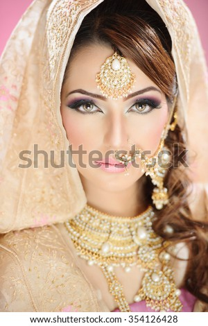Portrait of a beautiful ethnic female model in traditional bridal costume and jewellery - stock photo