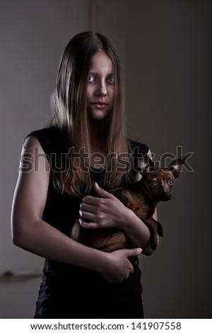Portrait of a beautiful evil teen girl with little doggy - stock photo