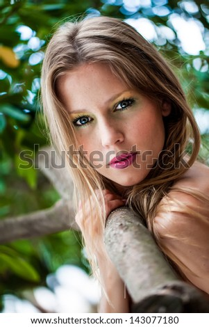 portrait of a beautiful fair haired young model with slight freckles in her face holding on to a tree branch and looking back intensely - stock photo