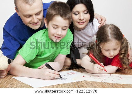 Portrait of a beautiful family: parents and children play together and draw