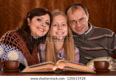 portrait of a beautiful family with a book drinking tea - stock photo