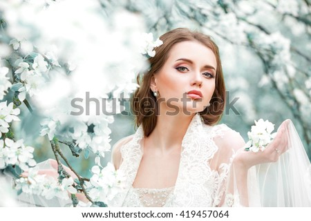 Portrait of a beautiful fashion bride, sweet and sensual. Wedding make up and hair. Flowers background. Art modern style. Blue eyes.  Against the background of blooming gardens of apple trees . - stock photo