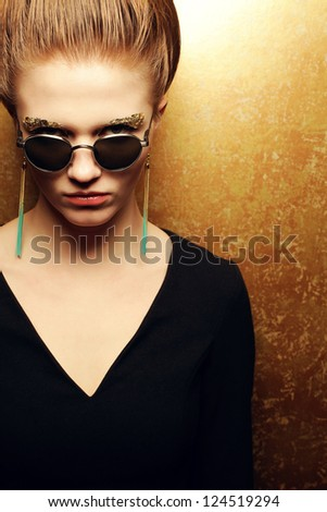 Portrait of a beautiful fashion red-haired model with a great makeup of golden foil posing over golden background and wearing vintage sunglasses. Closeup. Copyspace. studio shot - stock photo