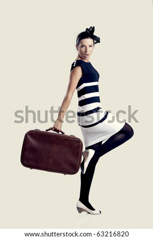 Portrait of a beautiful fashion woman posing and holding a old suitcase - stock photo