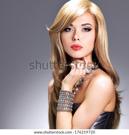 Portrait of a beautiful  fashion woman with bright makeup.  Pretty sexy face of a glamour girl posing at studio with silver accessor. - stock photo