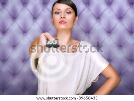 Portrait of a beautiful fashionable elegant woman with remote control choosing channels. Vintage luxury background - stock photo