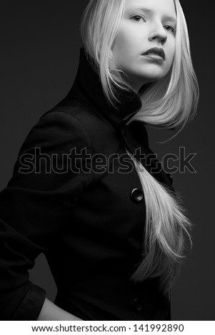 Portrait of a beautiful fashionable model with natural blond hair and great make-up in trendy black coat posing over dark gray background. Black and white (monochrome) studio shot - stock photo