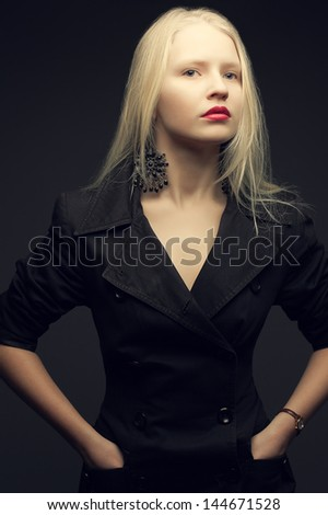 Portrait of a beautiful fashionable model with natural blond hair and great make-up in trendy black coat posing over dark gray background. Hands in pockets. Studio shot - stock photo