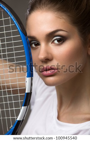 portrait of a beautiful female athletes with a tennis racket from a person in close-up - stock photo
