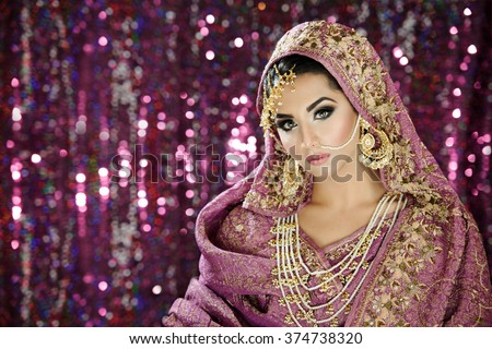 Portrait of a beautiful female fashion model in ethnic asian indian bridal costume with heavy jewellery and makeup - stock photo