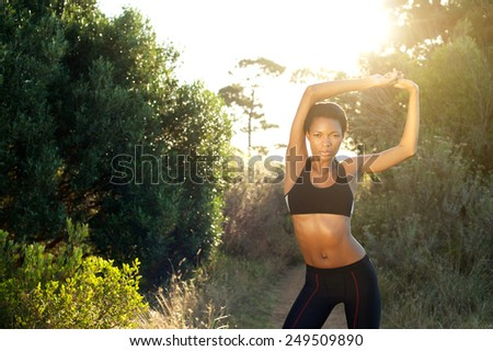 Portrait of a beautiful female fitness sports model stretching outdoors - stock photo