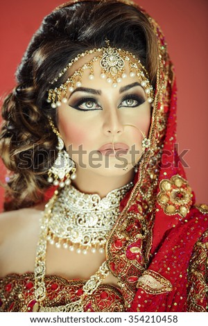 Portrait of a beautiful female model as a bride in traditional indian costume and jewellery - stock photo