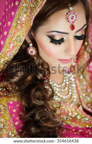 Portrait of a beautiful female model as an indian bride wearing traditional bridal costume and heavy jewellery and makeup - stock photo
