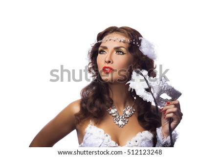 Portrait of a beautiful female model in a snowy white mask against white studio background. Christmas Holidays Party.