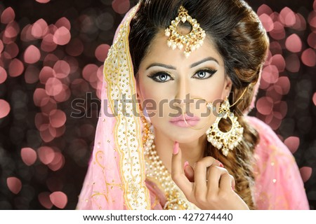 Portrait of a beautiful female model in classic indian asian bridal outfit looking sophisticated and classy with makeup and jewellery - stock photo
