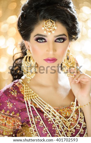 Portrait of a beautiful female model in ethnic indian bridal costume with heavy jewellery and traditional makeup