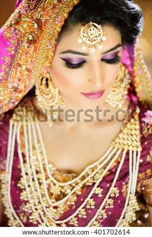 Portrait of a beautiful female model in ethnic indian bridal costume with heavy jewellery and traditional makeup - stock photo