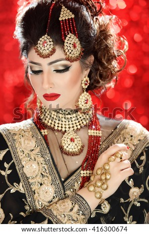 Portrait of a beautiful female model in tradition asian indian bridal costume with heavy jewellery and makeup - stock photo