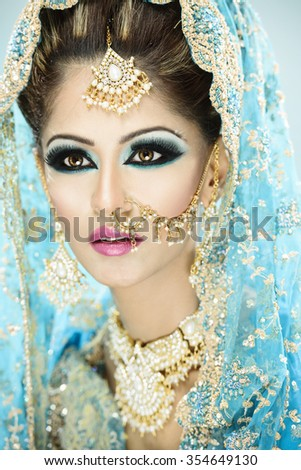 Portrait of a beautiful female model in traditional indian bridal costume and jewellery and makeup - stock photo