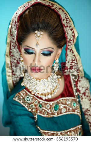 Portrait of a beautiful female model in traditional indian bridal costume with makeup and jewellery - stock photo
