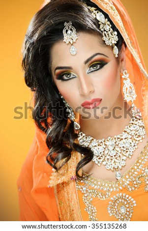 Portrait of a beautiful female model in traditional indian bride outfit with jewellery and makeup - stock photo