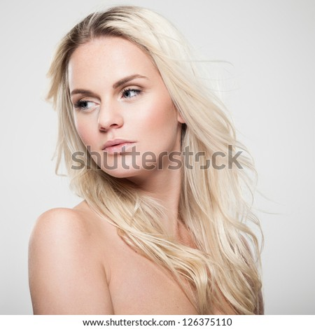Portrait of a beautiful female model on gray background - stock photo