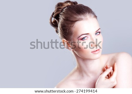 Portrait of a beautiful female model, smiles and looks at the camera - stock photo