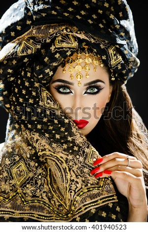 Portrait of a beautiful female model wearing a turban and veil in heavy eye makeup and jewellery