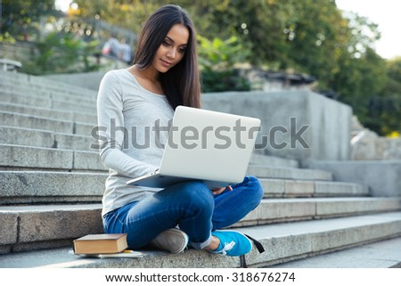 Portrait of a beautiful female student sitting on the city stairs and using laptop computer outdoors - stock photo