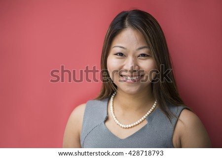 Portrait of a beautiful Filipino businesswoman in smart business suit leaning against a red wall.